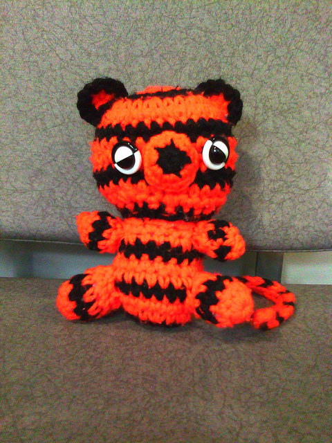 Boo-Boo the crochet tiger and traveling companions at a shoeshine stand in SFO
