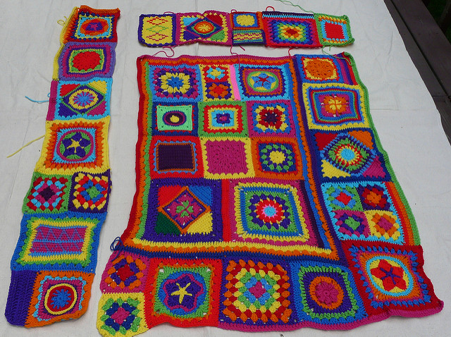 Crochet granny square afghan being pieced together