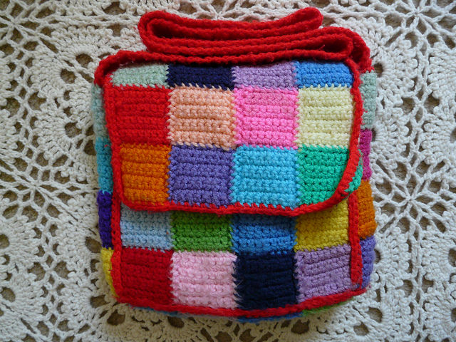 a multicolor crochet messenger bag made from crochet squares