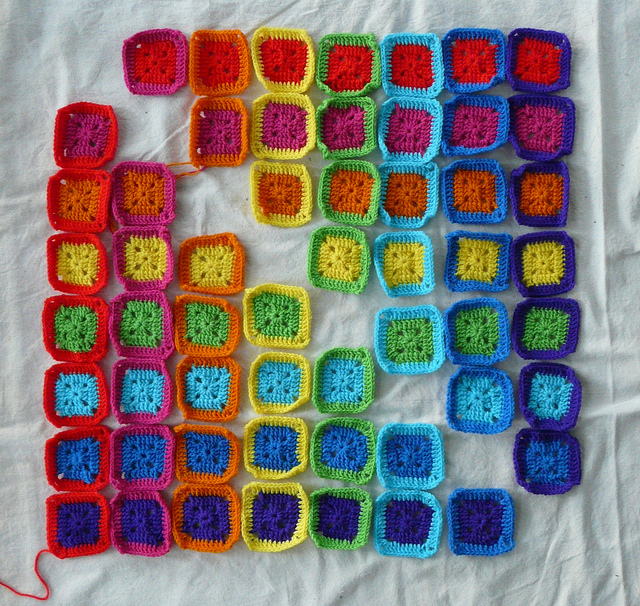 fifty-six three-round granny squares made using two eight colors for each square