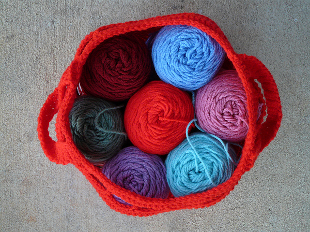 red yarn stash crochet bag filled with yarn