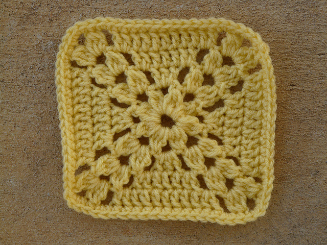 Crochet granny square worked in yellow yarn