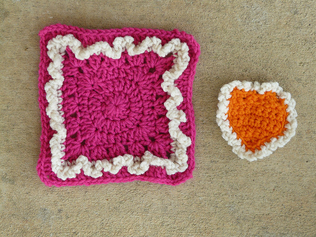 Pink ruffled crochet granny square with an orange crochet heart to be appliquéd