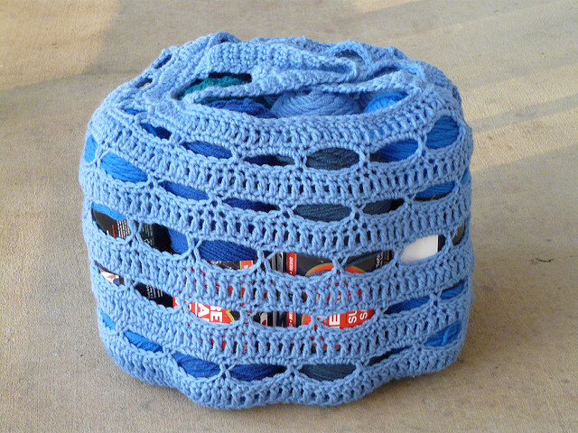 A blue crochet stash bag filled with yarn