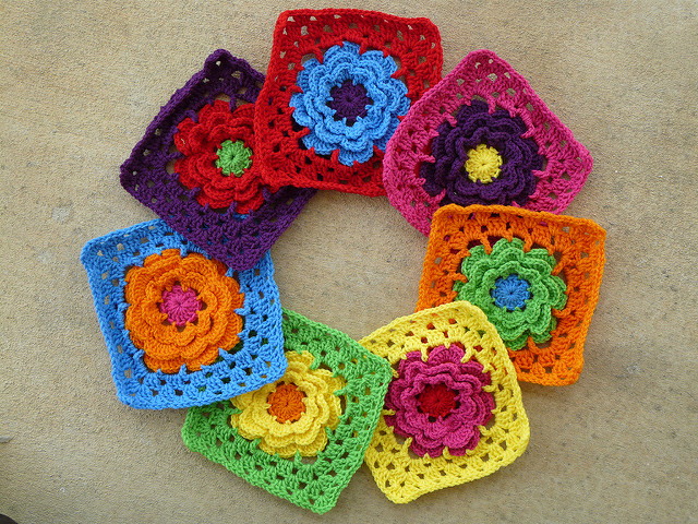 Seven bright color crochet squares arranged in a circle