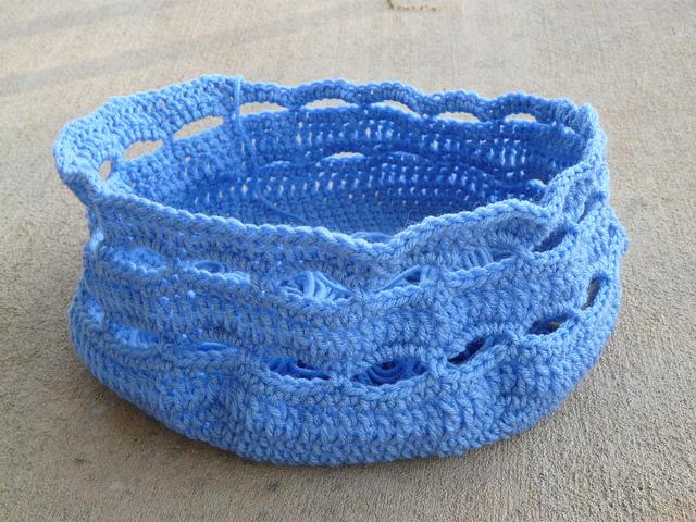 A blue crochet yarn stash bag