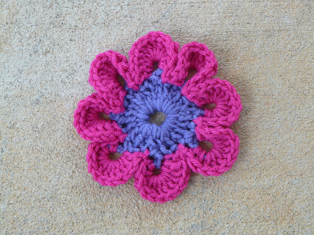 A crochet flower at the center of a crochet square