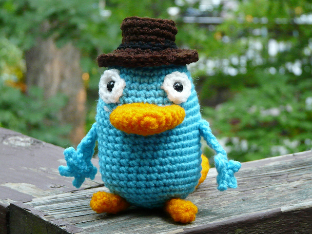 an amigurumi platypus with a crochet hat