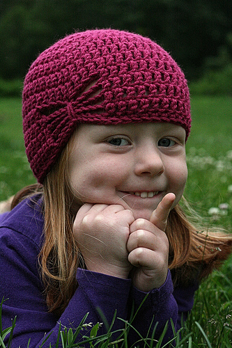 Happy little girl wearing a crochet hat, crochetbug, crochet beanie, crochet cap