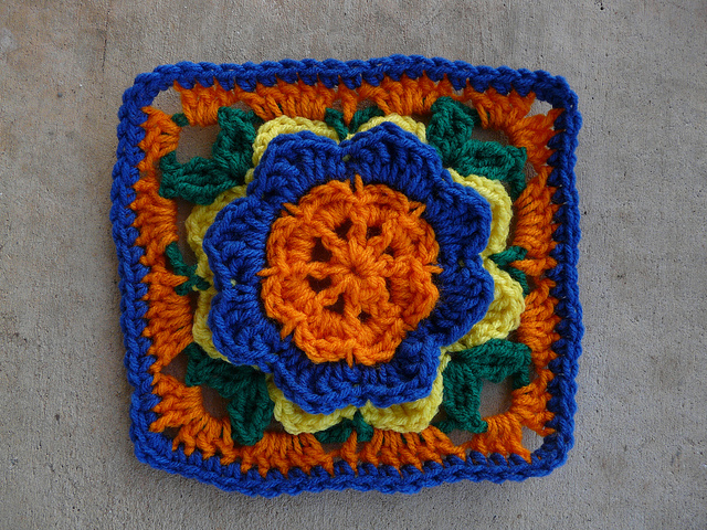 A crochet square with the color scheme from a box of oranges