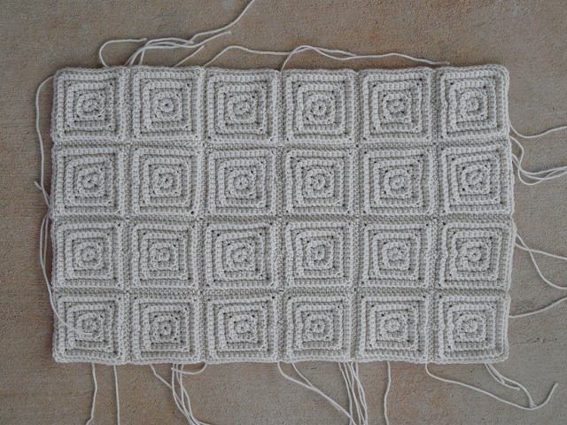 twenty-four small textured crochet square motifs