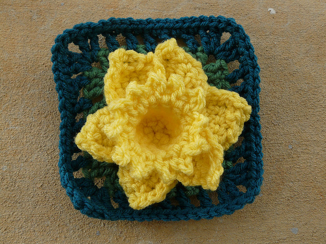 Crochet granny square with a crochet daffodil appliqué
