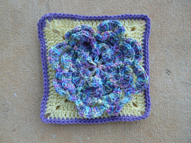 Crochet granny square with large crochet flower appliqué