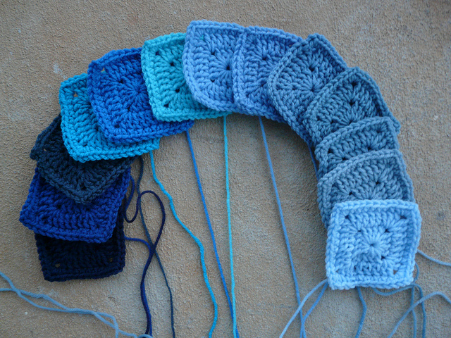 A rainbow of thirteen blue crochet squares
