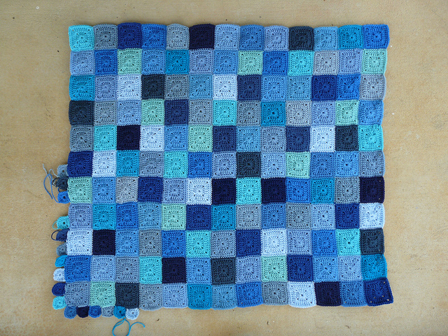 A crochet blanket made from many crochet squares made in varied shades of blue