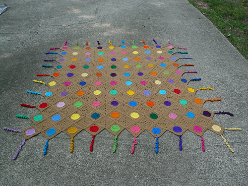 a crochet afghan made from multicolor circles and brown squares with hyperbolic crochet tassels