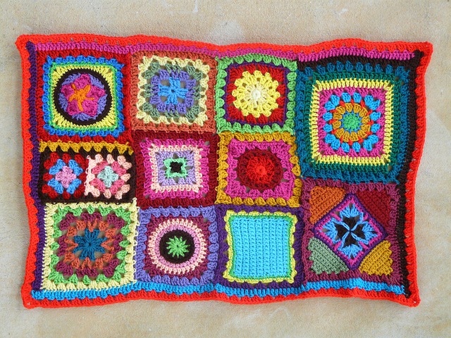 The squaring up progresses when I crochet a round of 3 dc clusters with a hot red yarn