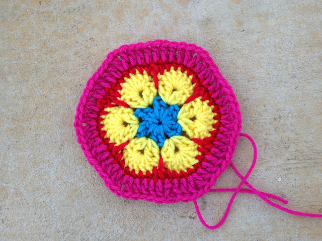 An African flower crochet hexagon with a pink border