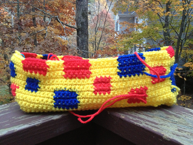 Progress on the yellow crochet purse with red and blue accents