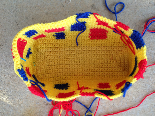 An overview of a yellow crochet purse with red and blue accents