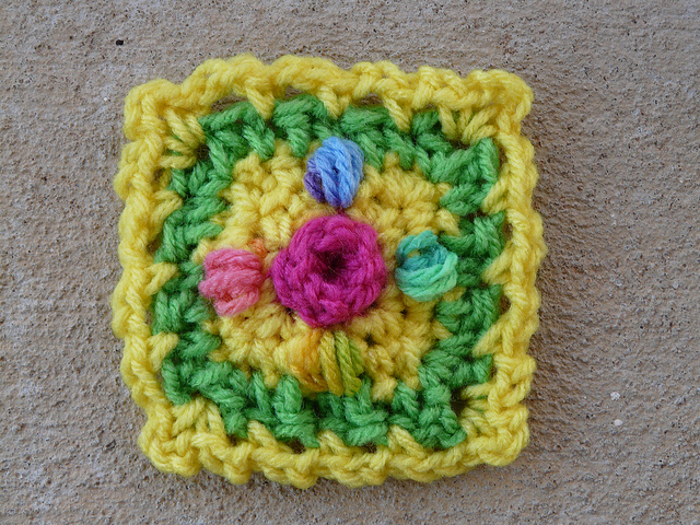 Small crochet square with a crochet rosebud center