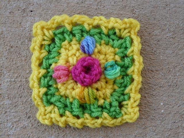 Small crochet square with a crochet rosebud center
