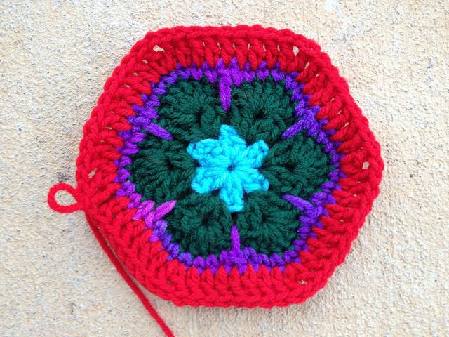 an African flower crochet hexagon with a red border