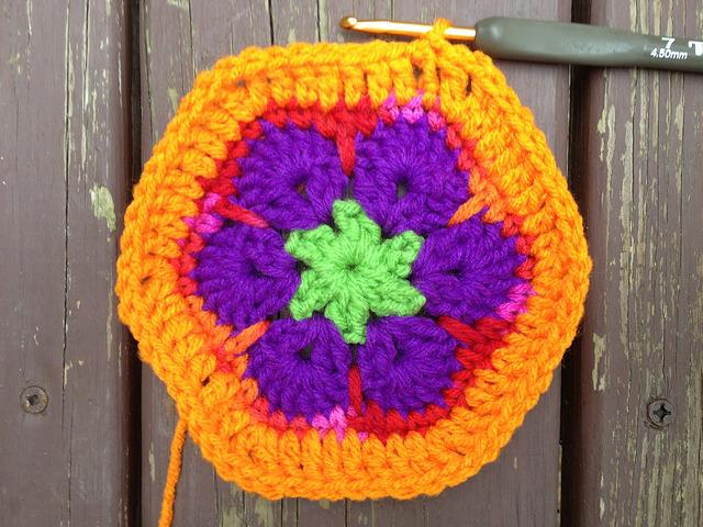 An African flower crochet hexagon with an orange border
