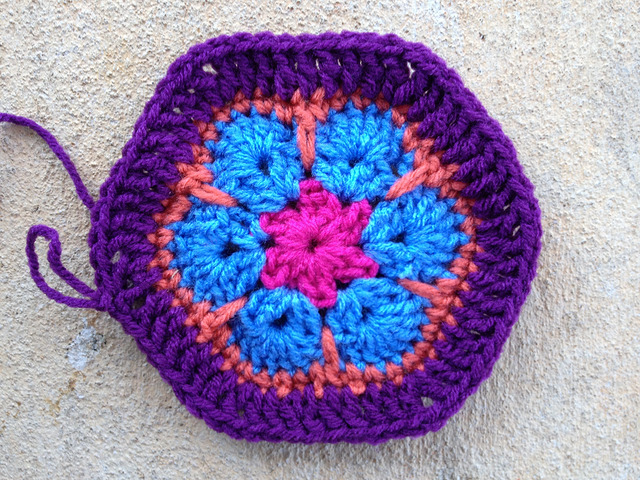 An African flower crochet hexagon with a purple border