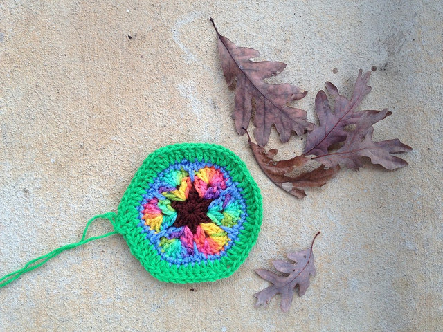 An African flower crochet hexagon with a green border
