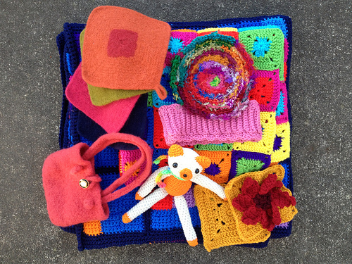 an assortment of color crochet projects including a felted purse, an amigurumi bear, felted crochet potholders, and a crochet sudoku afghan