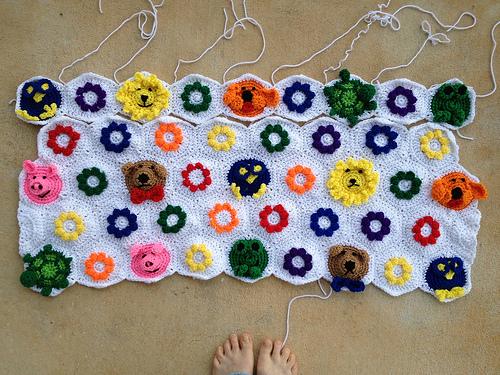 the first five rows of textured crochet flower hexagons and an assortment animal crochet hexagons