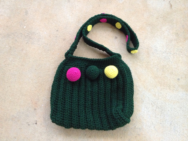 The green purse with crochet spots and crochet spheres ready for adventure