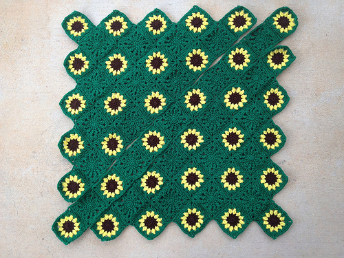 all of the sunflower crochet squares for a sarcoma awareness crochet blanket laid out and ready to be joined