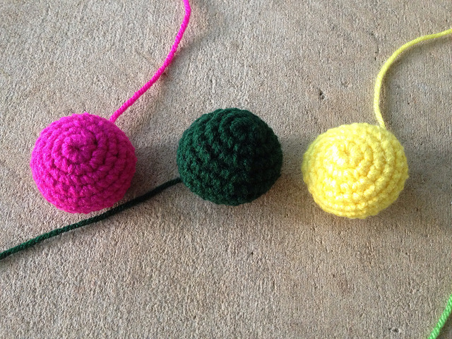 three crochet spheres worked in the same colors as the crochet spots