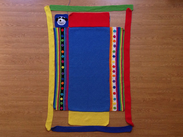 A nine panel project linus crochet blanket with the four crochet rectangles that form the crochet border