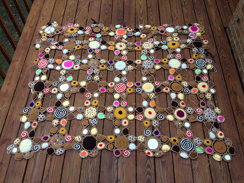 Forty-two of the forty-nine crochet cookie motifs needed for the crochet afghan