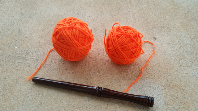 orange yarn wound on a nostepinne