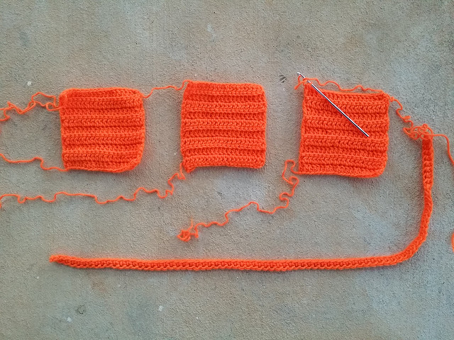 three orange crochet squares