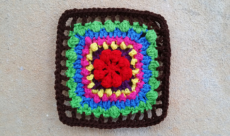 A crochet square worked in seven colors