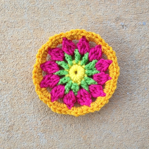 A crochet circle in yellow, green, pink, and gold
