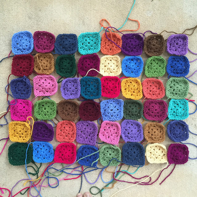 Forty-eight three-round granny squares in need of some yarn fairies to help weave in ends