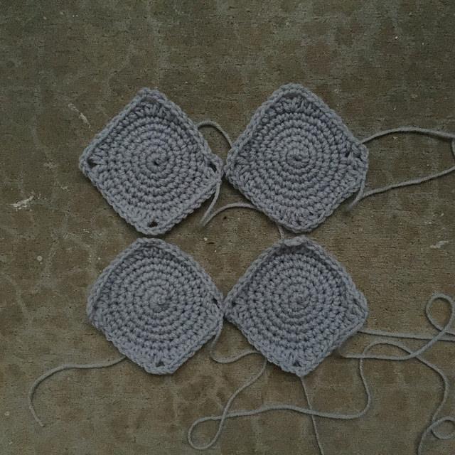 four gray crochet squares