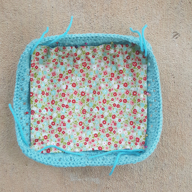 The crochet lunchbox lid with the lining pinned in and ready to be sewn