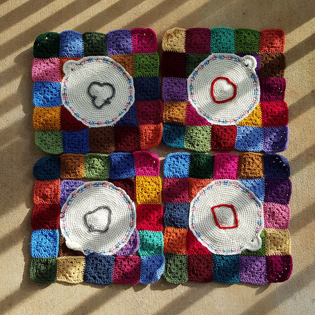 The four crochet corners of a future crochet blanket trimmed with granny squares