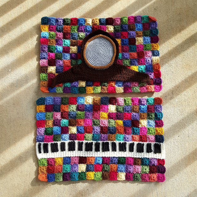 one round granny squares forming a back drop for a crochet keyboard and a crochet clock