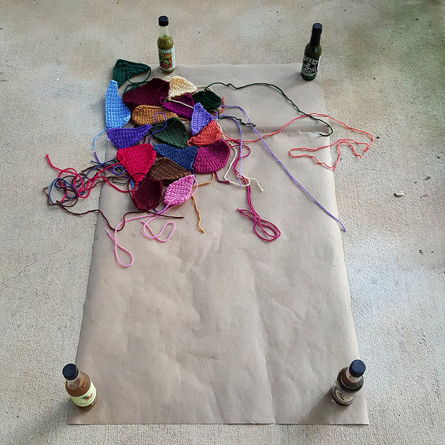 paper template with crazy quilt crochet pieces and hot sauce bottle weights