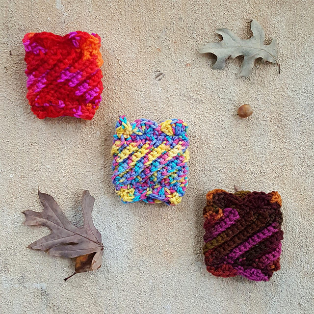 Three crochet coffee cup cozies that will be accessories for their coordinating bags