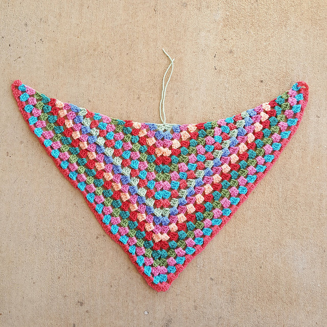 A multicolor crochet poncho ready for blocking