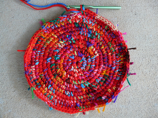 the start of a hot red and scrap yarn crochet basket